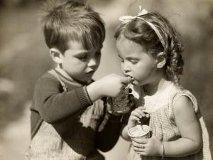 Boy Gives Ice Cream To Sister by George Marks