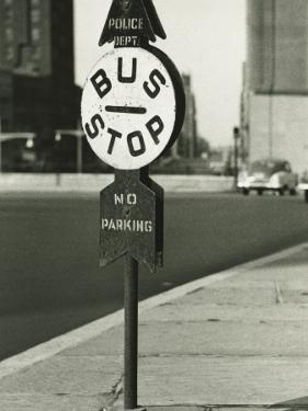 Bus Stop Sign on Sidewalk by George Marks