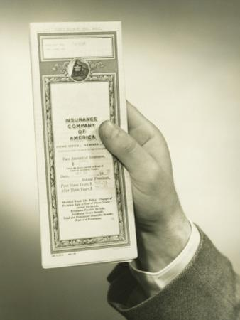 Businessman Holding Insurance Policy, Close-Up of Hand by George Marks