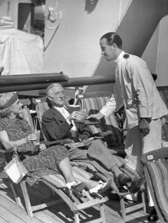 Elderly Couple Being Served Drinks on Deck of Cruise Ship by George Marks
