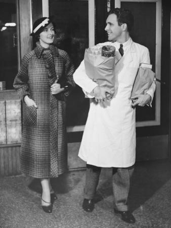 Grocery Store Clerk Carrying Packages For Elegant Woman by George Marks
