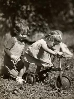 Little Boy and Girl Playing With Bicycle by George Marks