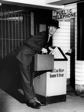 Man Throwing Away Newspaper by George Marks