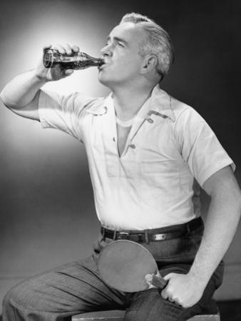Mature Man Holding Table Tennis Bat, Drinking Cola From Bottle by George Marks