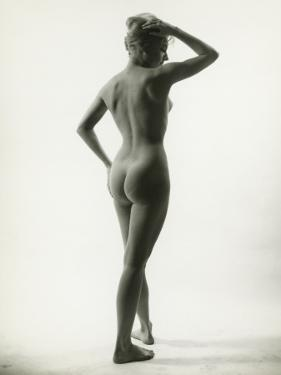 Naked Woman Posing in Studio, (Rear View) by George Marks