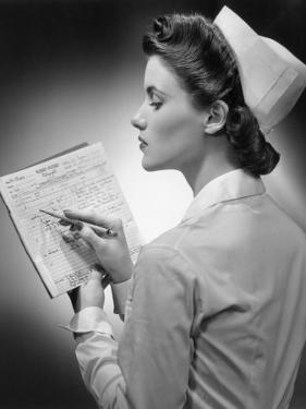 Nurse Reading Patient's Chart by George Marks