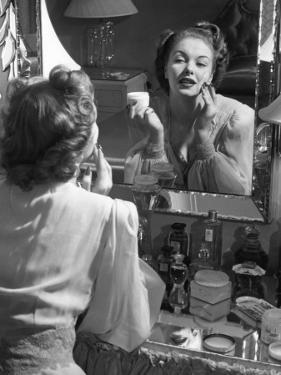 Woman Applying Make-Up in Front of Mirror by George Marks