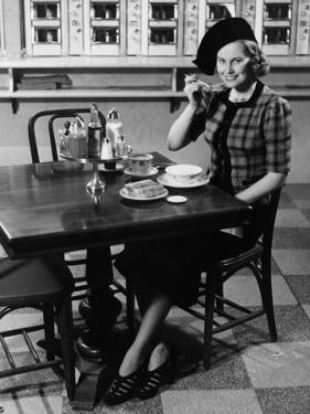 Woman in Fancy Hat Eating Breakfast in Bar by George Marks
