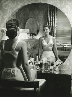 Woman in Underwear Sitting in Front of Vanity Table, Rear View by George Marks