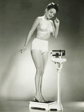 Woman in Underwear Standing on Scale by George Marks