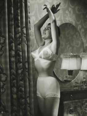 Woman in Underwear Stretching in Bedroom by George Marks