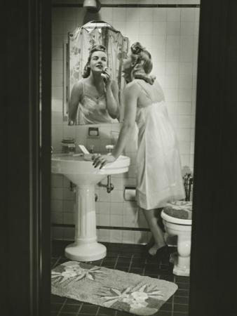 Woman Removing Make Up in Front of Mirror in Bathroom by George Marks