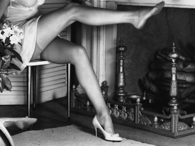 Woman Wearing Stockings Sitting By Fireplace by George Marks