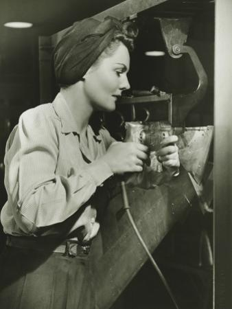 Woman Working With Electric Drill in Factory by George Marks