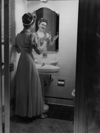 Young Woman Brushing Teeth in Bathroom by George Marks