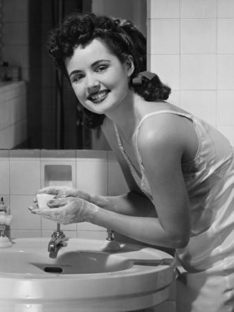 Young Woman Washing Hands in Bathroom, Portrait by George Marks