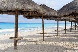 Palapas Lined up on the Beach, Cancun, Mexico by George Oze