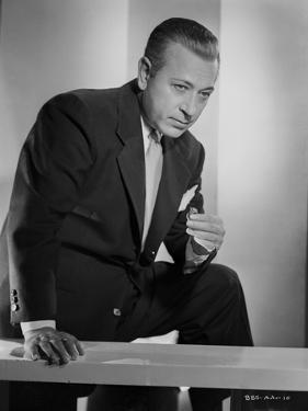 George Raft on the Table in Black Coat and Tie by E Bachrach