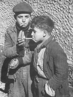 Two Homeless Boys Lighting Up American Cigarettes with British Matches by George Rodger