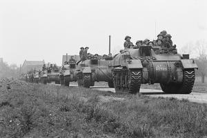 Members of the British 49th Armoured Personnel Carrier Regiment Riding Along a Line of Tanks by George Silk