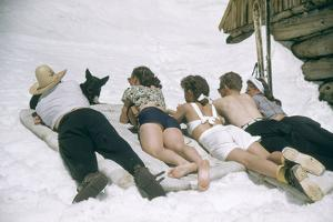 Skiers Sunbathing in Summer Fashions with Dog at Sun Valley Ski Resort, Idaho, April 22, 1947 by George Silk
