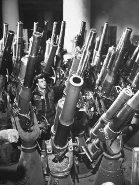 Brooklyn Naval Yard Worker Looking over a Storage of Guns by George Strock