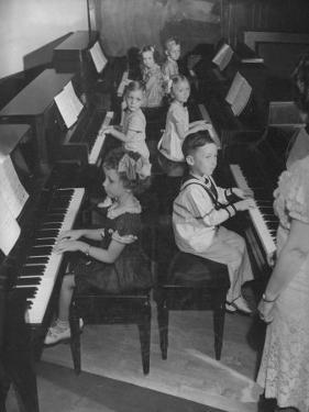 Children Taking Piano Lessons by George Strock