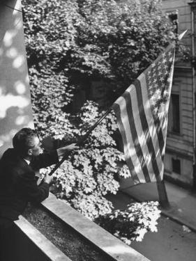 Man Hanging the American Flag Out of the Osteopath's Office Window During WWII by George Strock