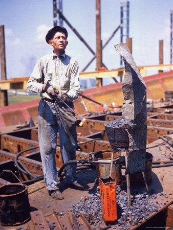 War Worker Holding Red Hot Metal Piece with Tongs at Shipyard