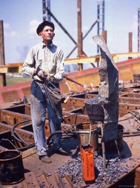 War Worker Holding Red Hot Metal Piece with Tongs at Shipyard by George Strock
