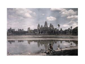 Person Sits by a Moat Which Surrounds the Towers of Angkor Vat by Gervais Courtellemont