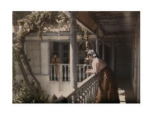 Two Women Look on to the Courtyard from a Balcony of a Christian Home by Gervais Courtellemont