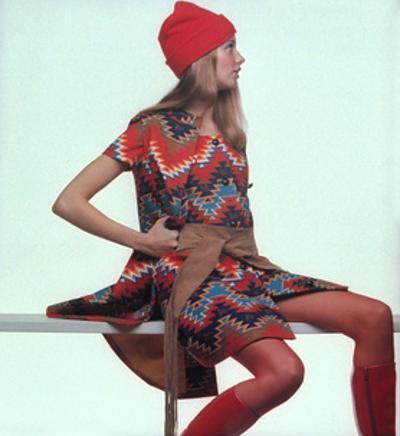 Model, Sitting on White Slat, Wears Bright Red and Blue Aztec-Print Sleeveless Coat