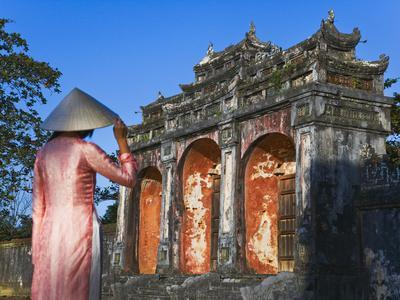 https://imgc.allpostersimages.com/img/posters/girl-in-ao-dai-traditional-vietnamese-long-dress-and-conical-hat-at-minh-mang-tomb-vietnam_u-L-PHAQIE0.jpg?p=0