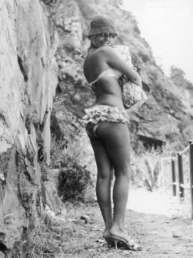 Girl in Bikini Walks Along a Cliff Path on a Fine Summer Day