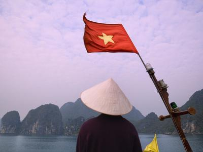 https://imgc.allpostersimages.com/img/posters/girl-with-conical-hat-on-a-junk-boat-with-national-flag-and-karst-islands-in-halong-bay-vietnam_u-L-PHAQFU0.jpg?p=0