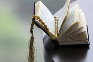 An open Holy Quran and Muslim prayer beads by Godong