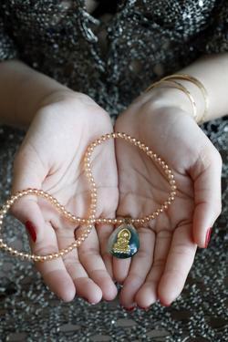 Buddhist woman with a Buddha pendant, Vung Tau by Godong