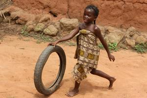 Child playing with a tyre, Tori, Benin by Godong