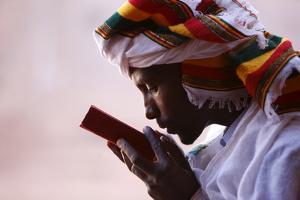 Faithful kissing a Bible outside a church in Lalibela, Ethiopia by Godong