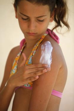 Girl putting on sunblock by Godong