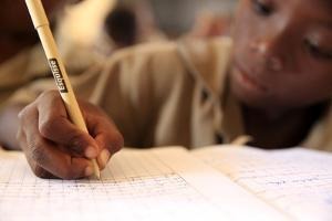 Pupil taking notes in French class in African primary school, Lome, Togo by Godong