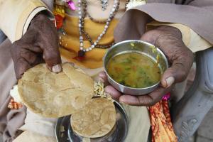 Sadhu eating vegetarian food, Dauji, Uttar Pradesh, India by Godong