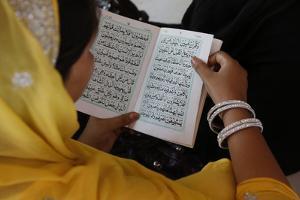 Woman reading Kuranic scriptures in Nizamuddin Dergah, Delhi, India by Godong