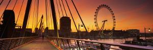 Golden Jubilee Bridge across a Thames River, Ferris Wheel in Back, London, England