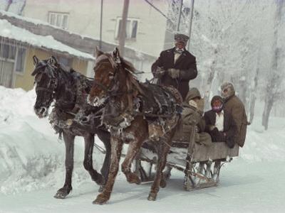 A Sleigh Serves as a Taxi on a Snow-Covered Village Street