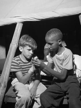 African American Camper Helps a White Bubby with His Bandaged Hand by Gordon Parks