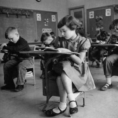 Cute Little Girl Busily at Work, Sitting in a Desk Chair in a Schoolroom, Other Pupils at Work Too