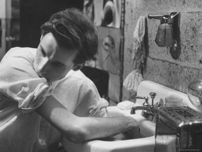 Pianist Glenn Gould Soaking His Hands in Sink to Limber Up His Fingers Before in Studio