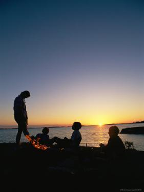 A Family is Silhouetted Around a Campfire by Gordon Wiltsie